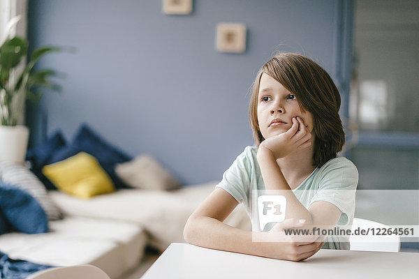 Porträt eines traurigen Jungen  der zu Hause am Tisch sitzt.