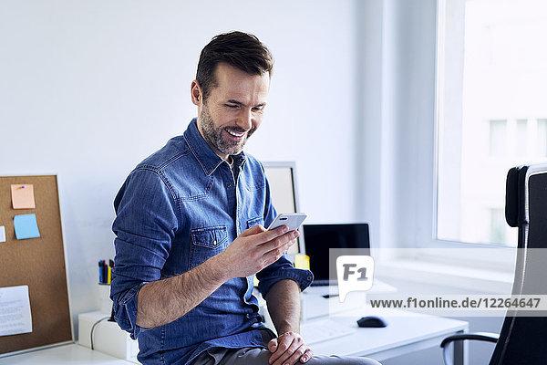 Lächelnder Mann mit Handy am Schreibtisch im Büro
