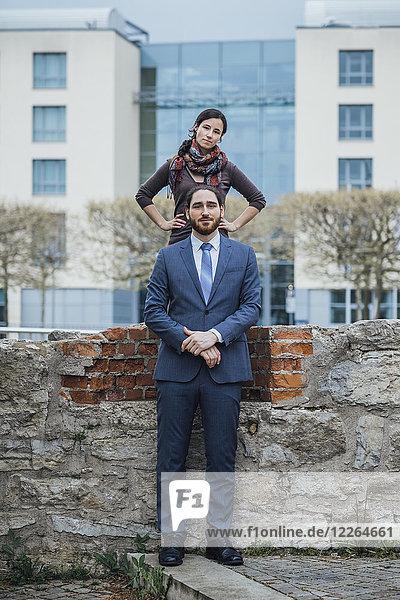 Porträt eines Geschäftsmannes und einer Geschäftsfrau an einer Wand vor dem Bürogebäude