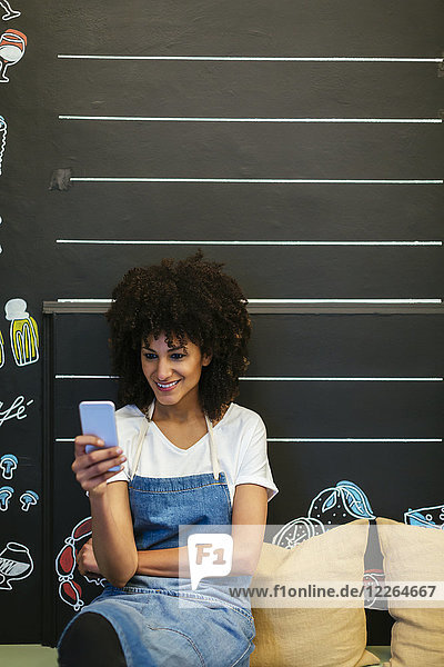 Lächelnde Frau sitzt auf einer Bank in einem Geschäft mit Handy