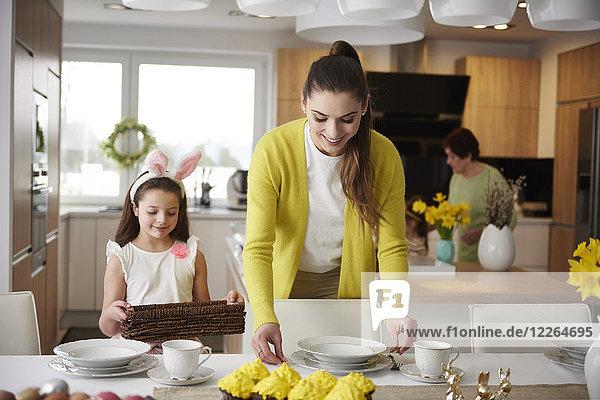 Lächelnde Mutter und Tochter decken gemeinsam den Tisch zu Hause.
