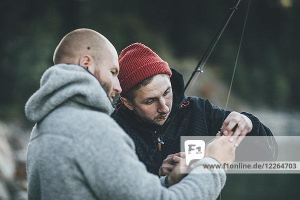 Junger Mann hilft Freund mit Angelrute