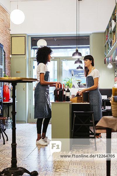 Zwei Frauen  die in einem Laden reden.