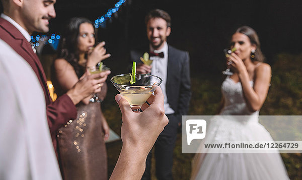 Happy friends drinking cocktails on a night field wedding party