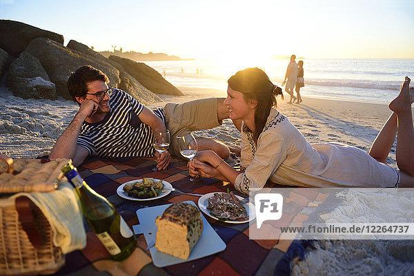 Glückliches Paar beim Picknick am Strand bei Sonnenuntergang