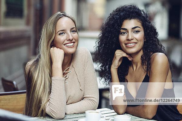 Porträt von zwei Freunden  die im Straßencafé sitzen und etwas beobachten