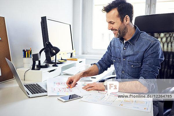 Lächelnder Webdesigner bei der Arbeit am Schreibtisch im Büro