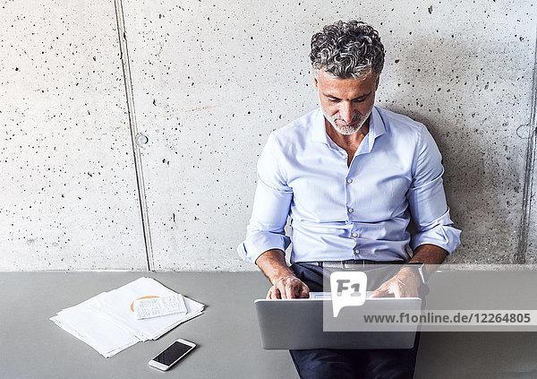 Reife Geschäftsleute sitzen auf dem Boden mit dem Laptop