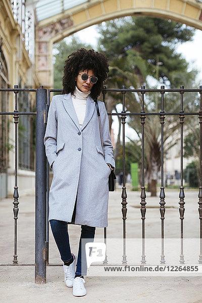 Spanien  Barcelona  Frau mit Sonnenbrille an einem Tor stehend