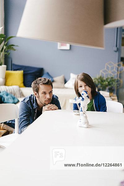 Vater und Sohn schauen auf den Roboter auf dem Tisch zu Hause