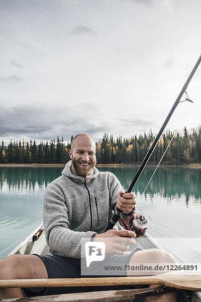 Kanada  British Columbia  Porträt des glücklichen Mannes beim Kanufischen auf dem Boya Lake