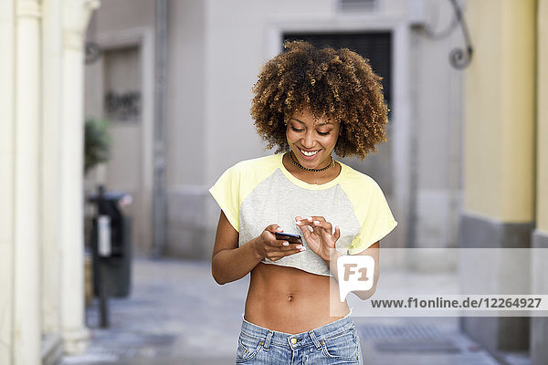 Smiling woman with afro hairstyle using smartphone outdoors