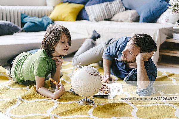 Vater und Sohn essen Pizza neben dem Globus auf dem Boden zu Hause