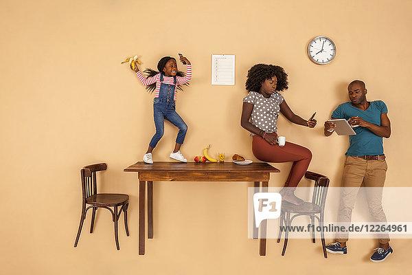 Familie beim Frühstück in der Küche  Überprüfung der mobilen Geräte