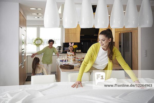 Lächelnde Frau  die die Tischdecke zu Hause mit der Familie im Hintergrund ausbreitet.