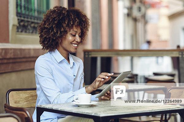Lächelnde Frau mit Afro-Frisur sitzend im Outdoor-Café mit Tablette