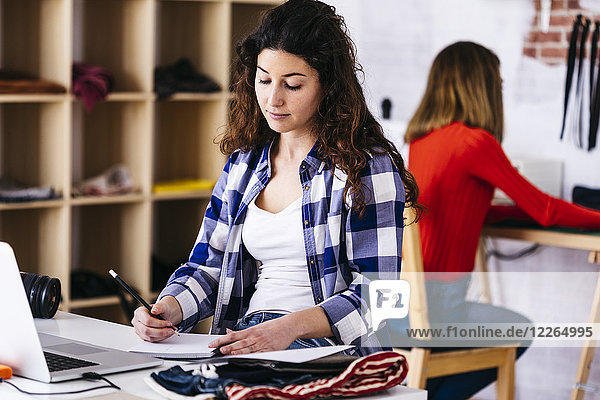 Fashion designer with laptop taking notes in studio