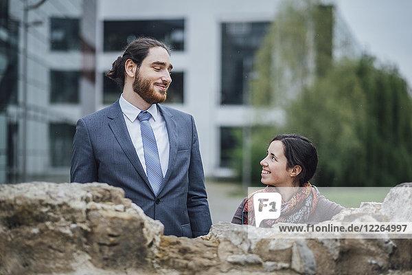 Lächelnder Geschäftsmann und Frau hinter einer Wand vor dem Bürogebäude
