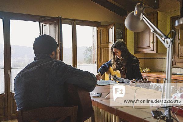 Junges Paar spielt Gitarre zu Hause am Tisch