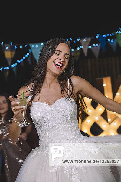 Happy bride laughing and dancing while holding cocktail on an outdoor night party