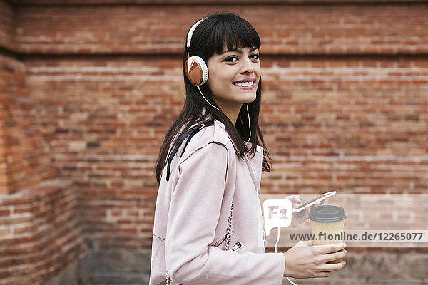 Porträt der lächelnden Frau mit Kaffee  Handy und Kopfhörer an der Ziegelwand