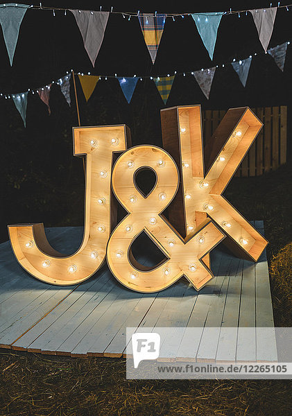 Handmade wooden letters illuminated with light bulbs on a night field party