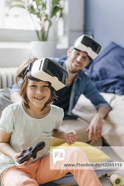 Porträt eines glücklichen Jungen und Vaters mit VR-Brille beim Videospiel zu Hause