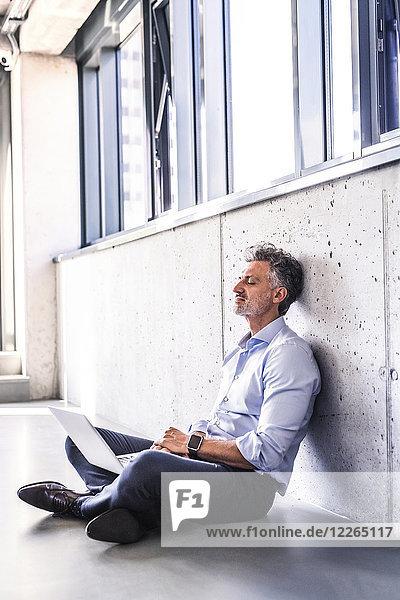 Erwachsener Geschäftsmann mit Laptop  der auf dem Boden sitzt und sich an die Wand lehnt.