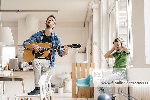 Erschrockener Sohn  der sich die Ohren zuhielt und zu Hause Gitarre spielt.