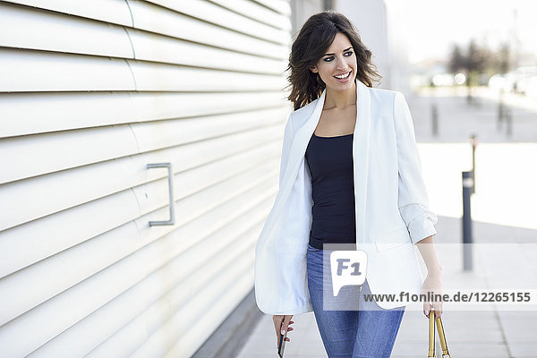 Portrait of smiling businesswoman with cell phone ang handbag watching something