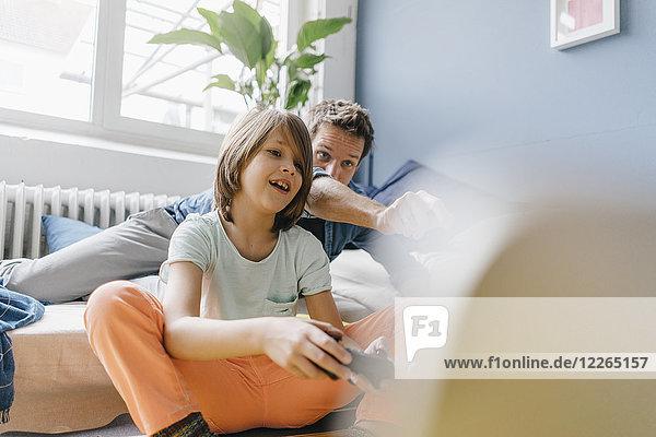 Vater und Sohn beim gemeinsamen Videospiel zu Hause