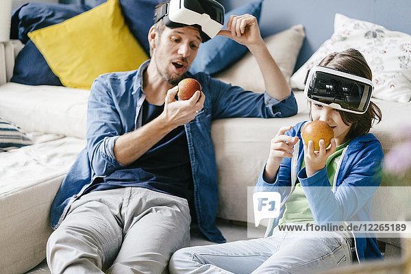 Vater und Sohn mit VR-Brille und Äpfel essen zu Hause