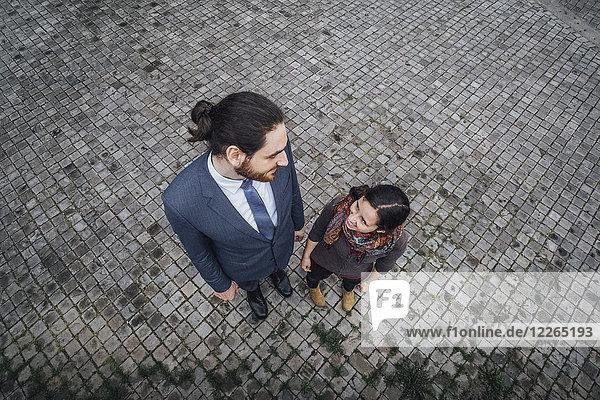 Frau und Geschäftsmann stehen auf Kopfsteinpflaster und lächeln sich an.