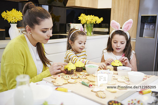 Mutter mit Töchtern  die Osterkekse und Muffins in der Küche dekorieren.