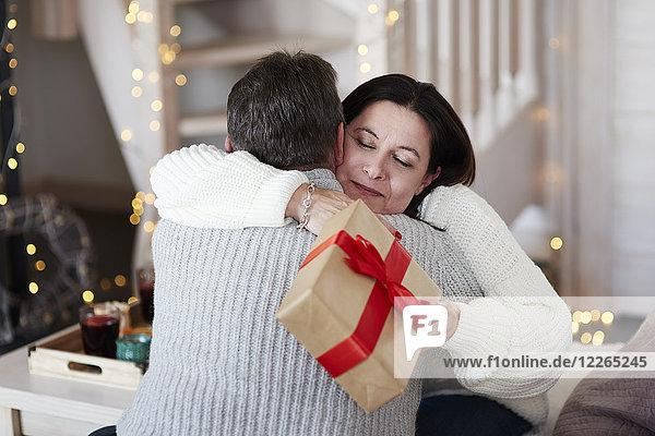 Fröhliches reifes Paar mit Geschenkschachtel im Wohnzimmer