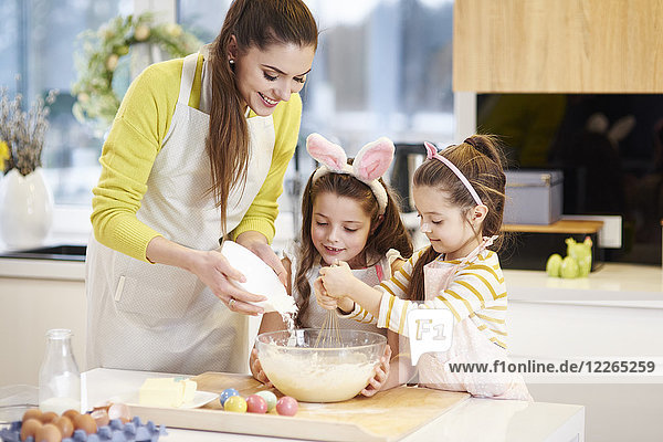 Mutter und Töchter backen gemeinsam Osterplätzchen in der Küche