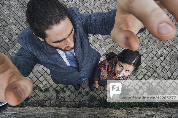 Großer Geschäftsmann auf Kopfsteinpflaster neben kleiner Frau stehend