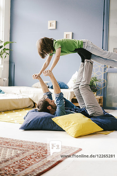 Glücklicher Vater und Sohn beim Spielen zu Hause