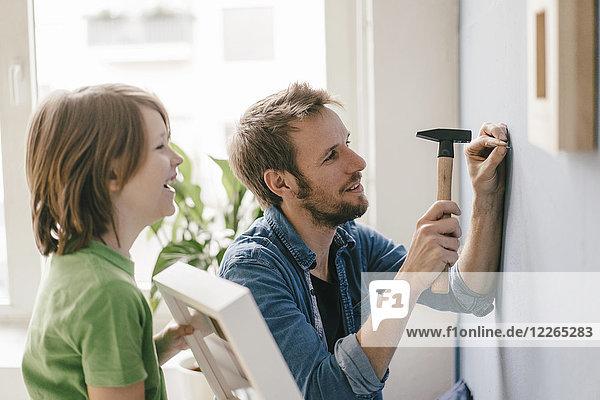 Sohn beobachtet Vater  wie er zu Hause einen Nagel in die Wand schlägt.