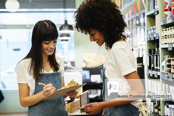Zwei lächelnde Frauen in einem Laden mit Zwischenablage