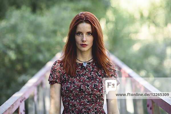 Portrait of redheaded young woman standing on footbridge in nature