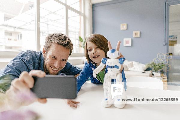 Glücklicher Vater und Sohn nehmen einen Selfie mit Roboter zu Hause mit auf den Tisch