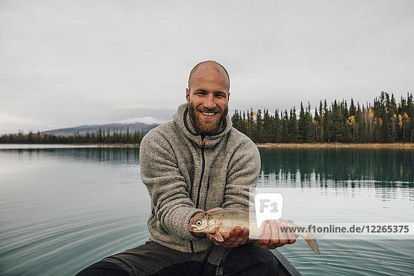 Kanada  British Columbia  Porträt eines lächelnden Mannes im Kanu mit Fisch auf dem Boya Lake