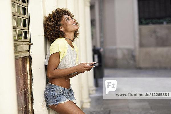 Lächelnde Frau mit Afro-Frisur hält Smartphone im Freien