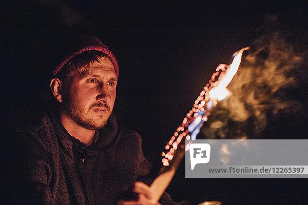 Mann mit brennendem Baumstamm bei Nacht