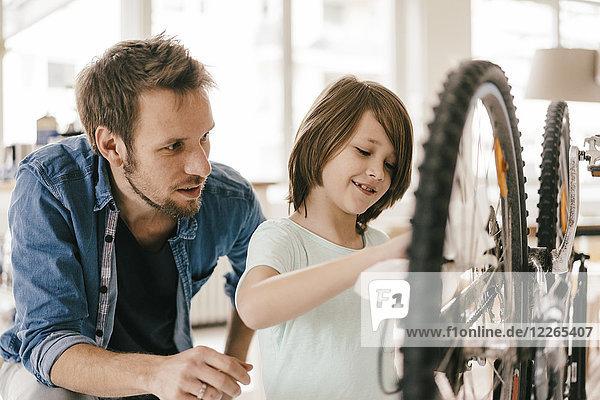 Vater und Sohn reparieren gemeinsam das Fahrrad zu Hause