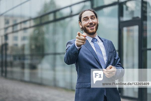 Porträt eines glücklichen Geschäftsmannes  der mit dem Finger nach draußen zeigt.
