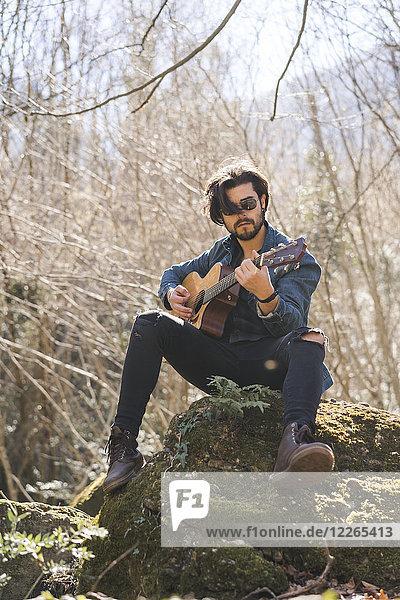 Junger Mann sitzend auf einer Rockgitarre