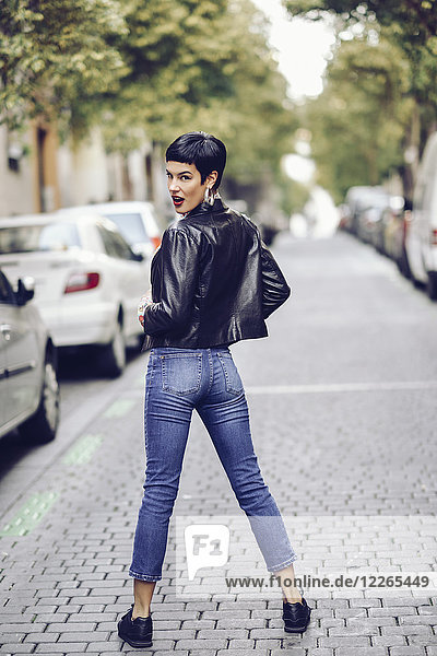 Modische junge Frau in Jeans und Lederjacke stehend auf der Straße
