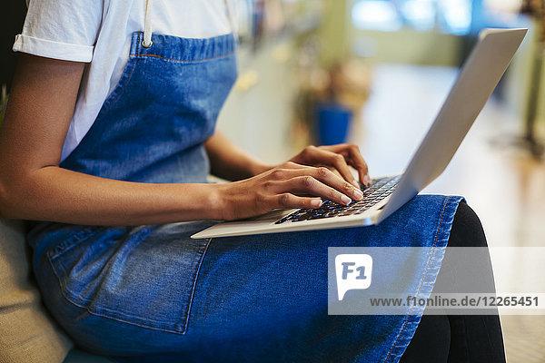 Nahaufnahme einer Frau mit Laptop in einem Geschäft